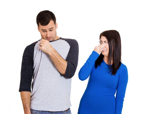 Woman looking at man who sniffs himself