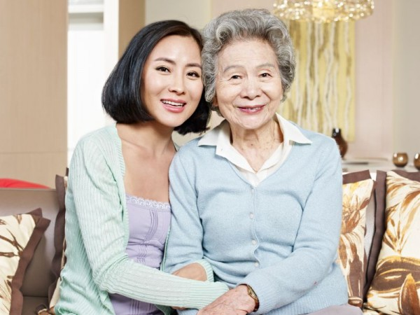 sirabee_asian mother and adult daughter sitting on couch smiling