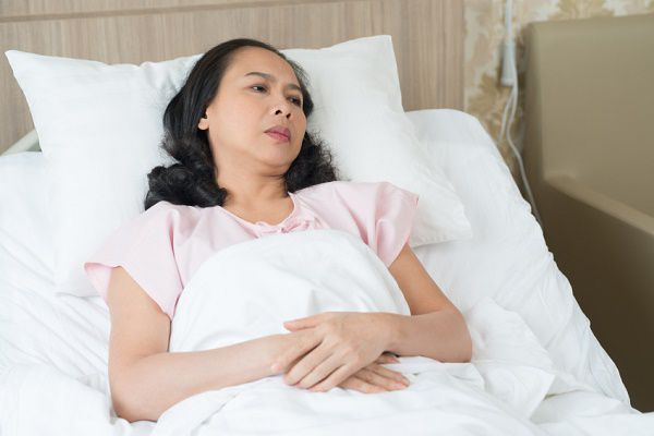 Senior Vietnamese, woman lying on bed in the hospital