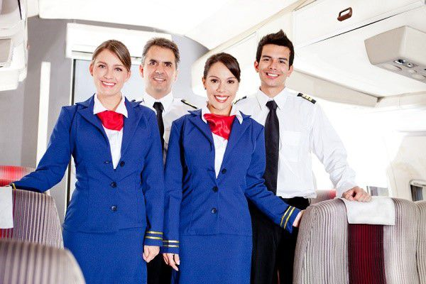 Friendly cabin crew in an airplane smiling