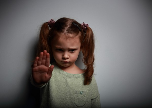 Kid girl showing hand signaling to stop violence and pain and lo