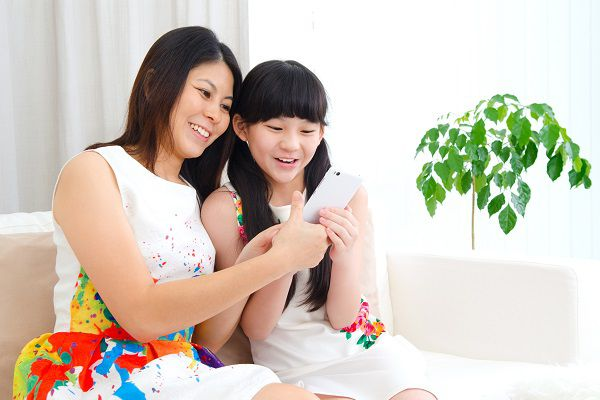 Beautiful asian woman and daughter having fun playing smartphone