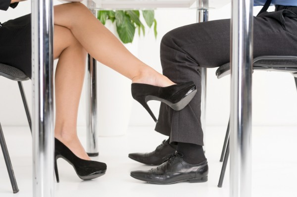 The Office Affair. Woman's foot looking for man's foot under a business table.