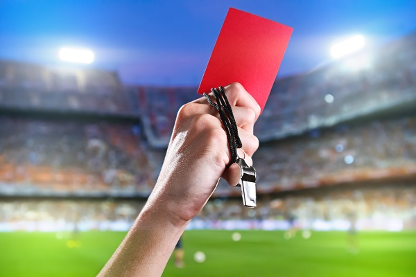 Referee holding up a red card and whistle inside a stadium