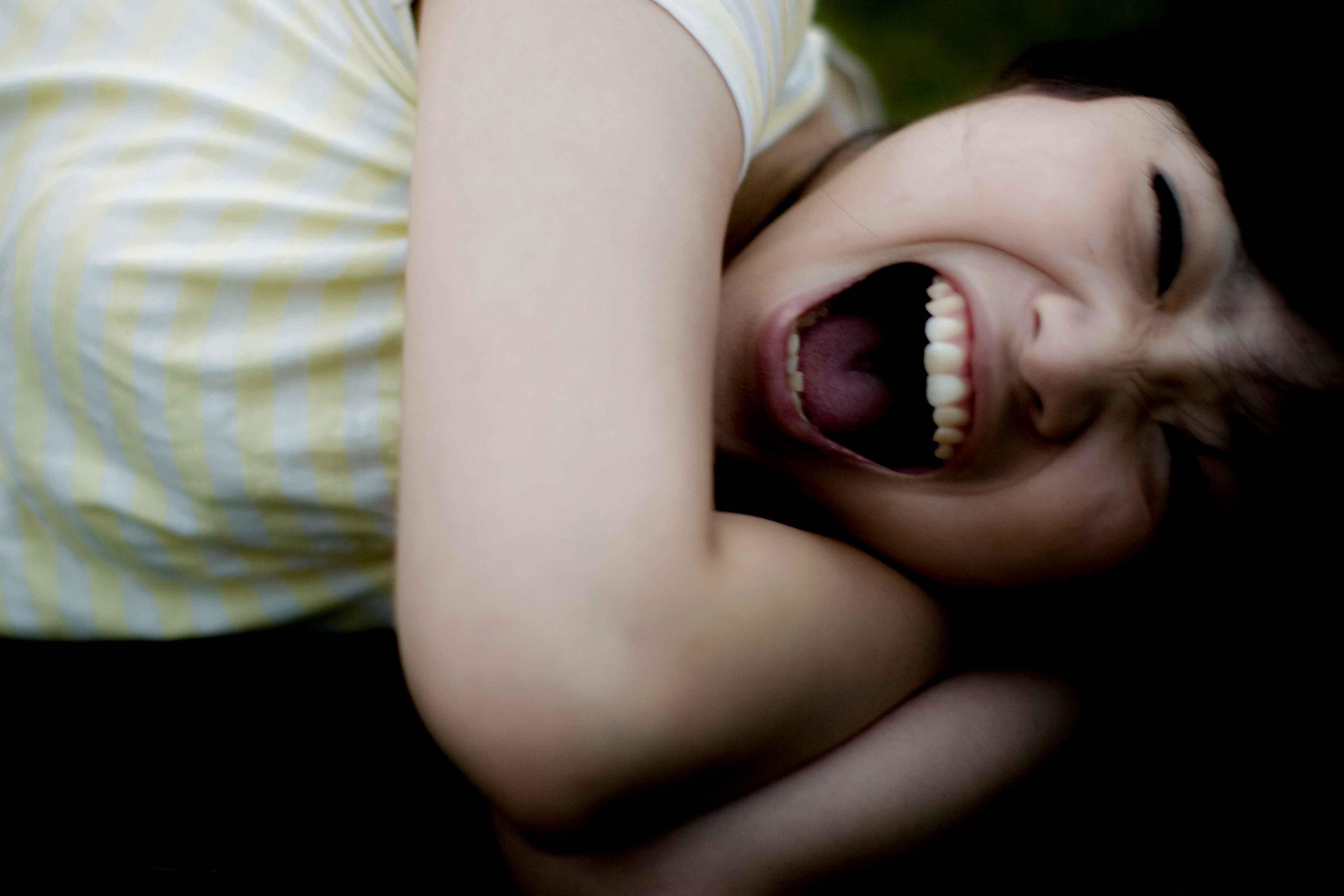 横たわり叫ぶ女性