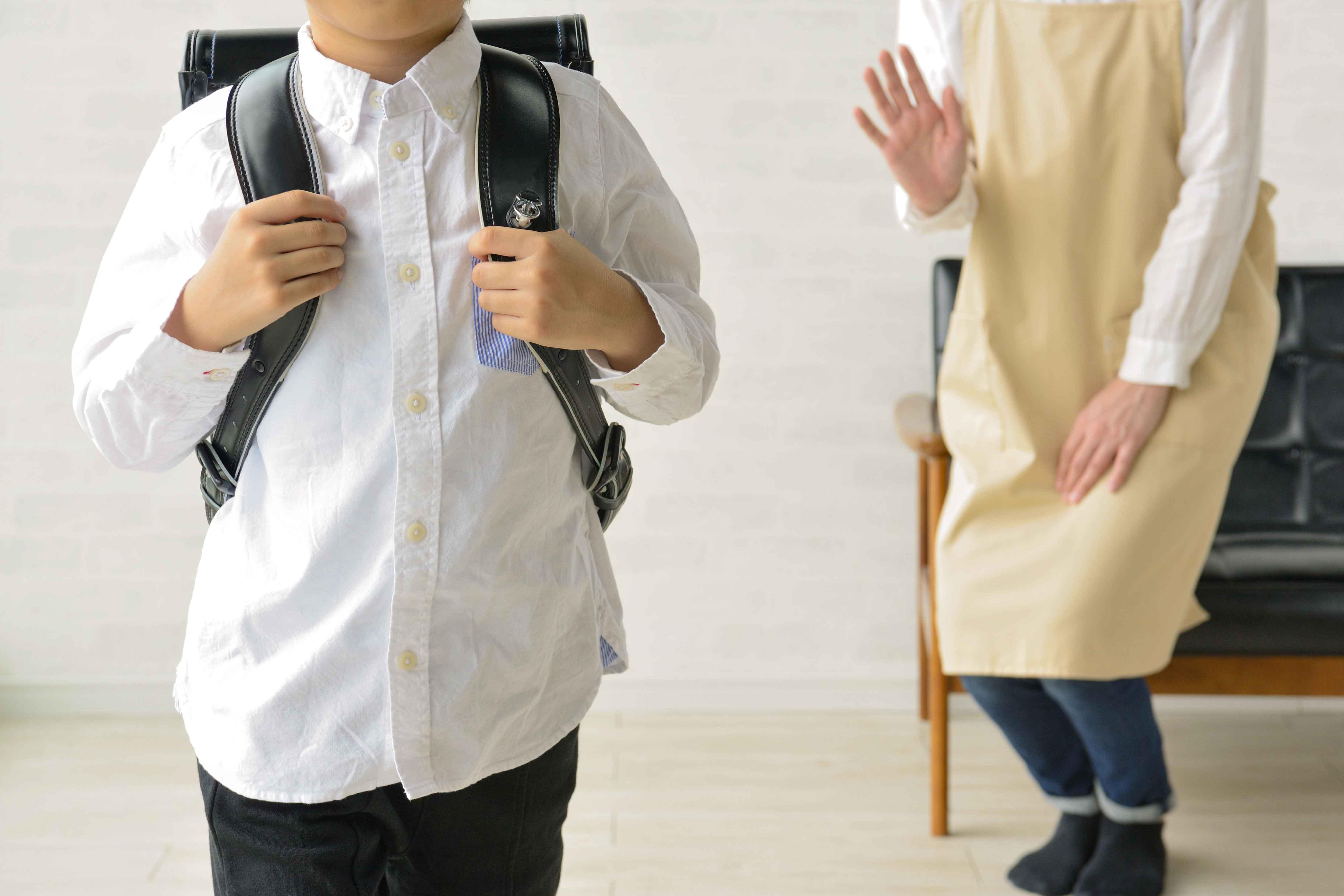 学校に行く少年と見送る母親