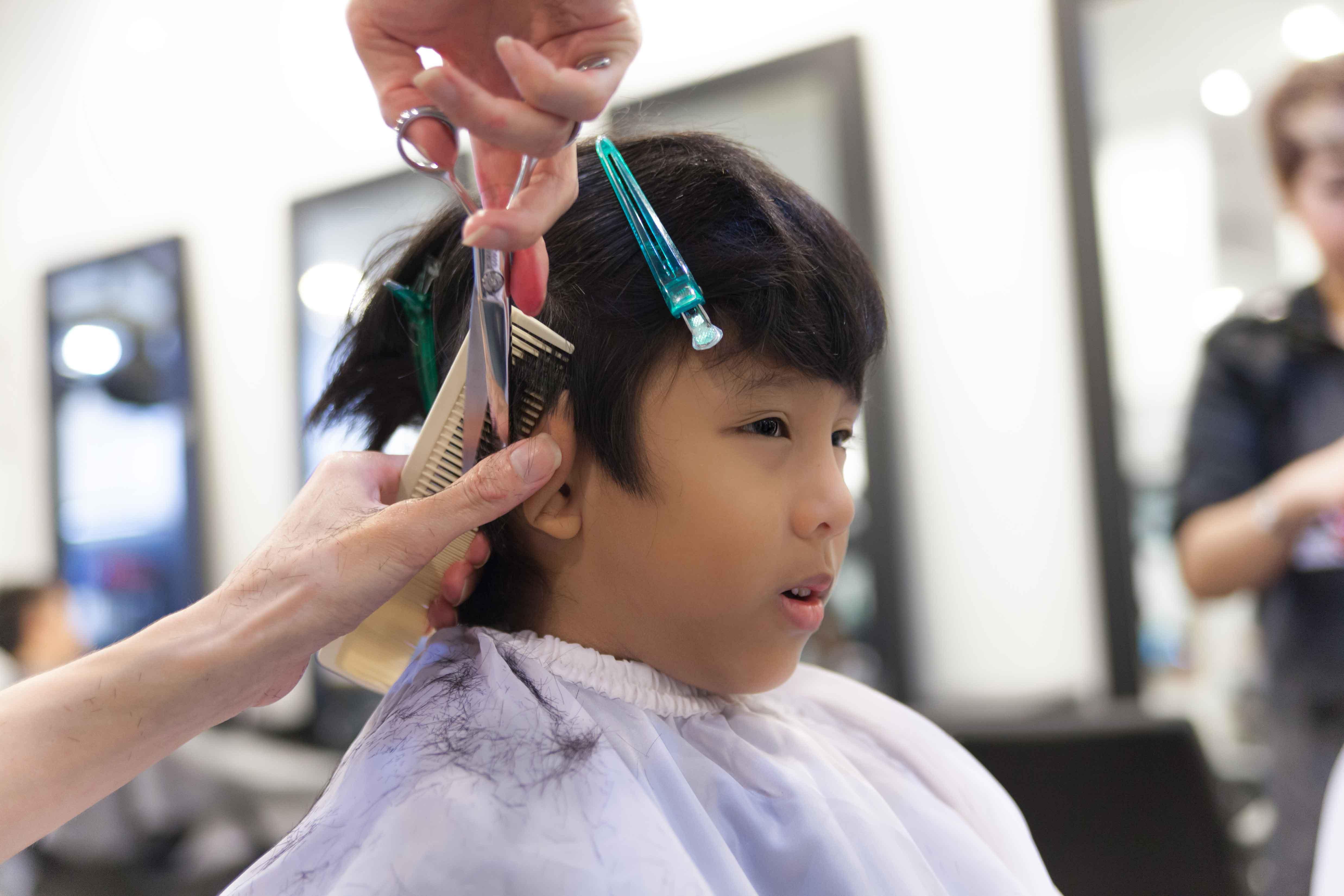 床屋で散髪される少年