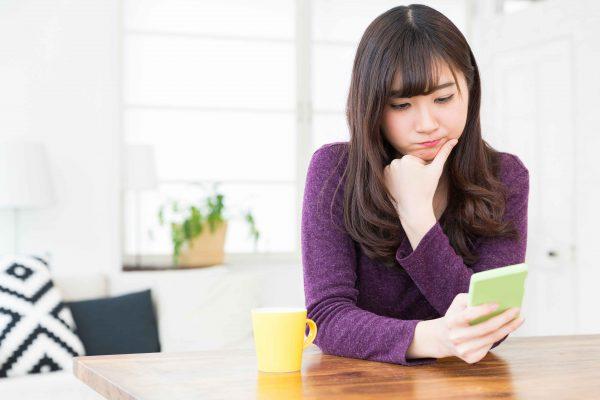スマートフォンを見て悩む女性