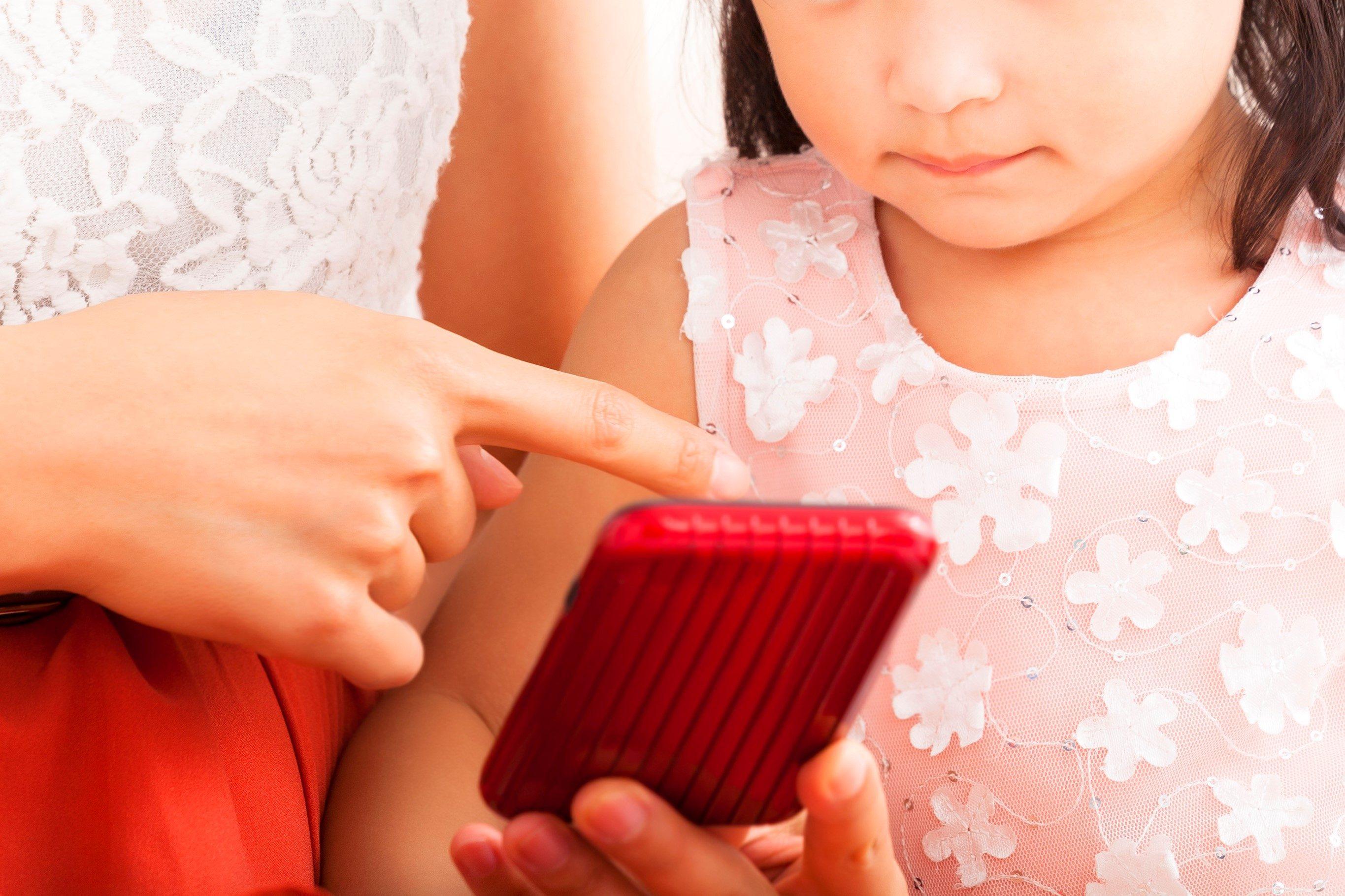 携帯電話の使い方を教える母娘