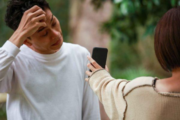 スマートフォンの画面を男性に見せる女性