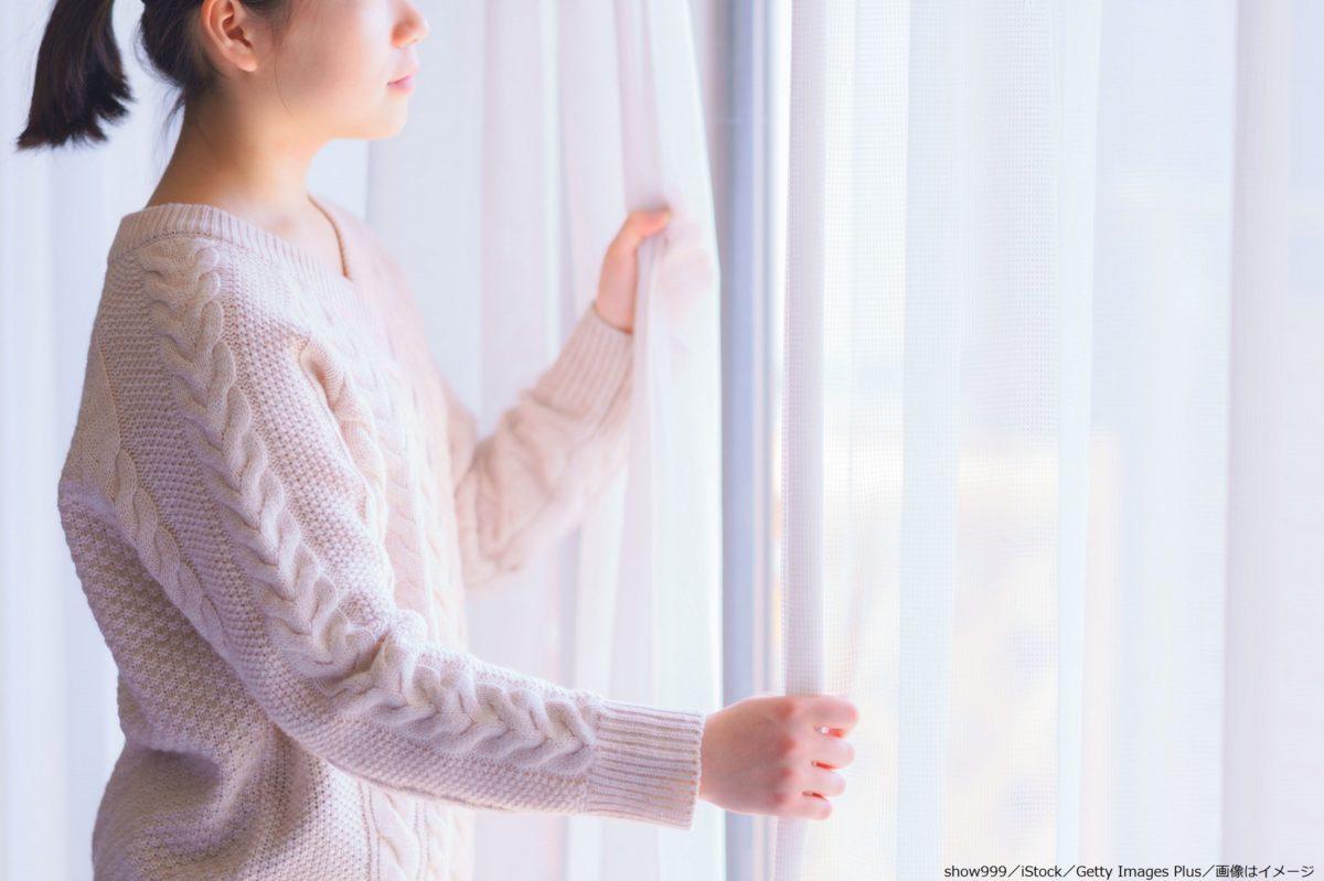 窓の外を眺める女性